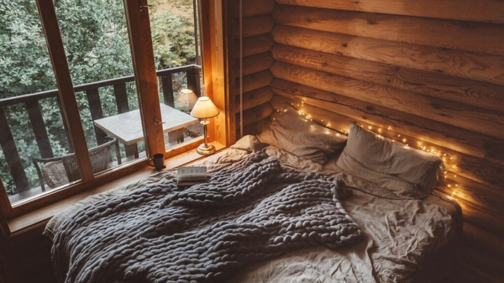 The use of fairy lights behind the bed gives this room a romantic, almost magical feel.  The log walls and large window looking over the forest add to this natural look.