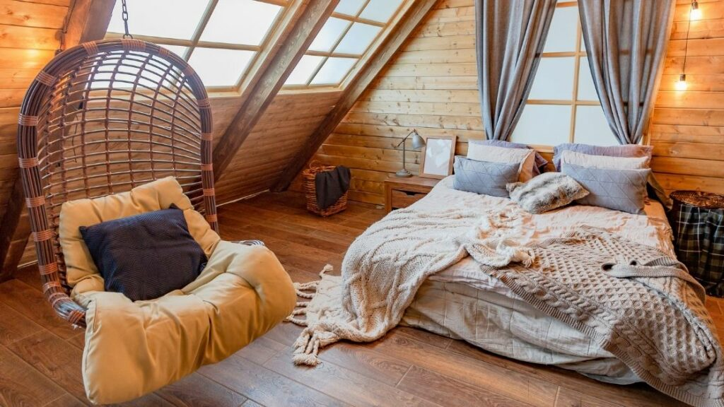 This attic room is full of natural light bouncing off the wooden walls and floor.  The lights and the floating chair remind me of the attic of an old barn.  This space would be a fantastic room for a romantic weekend.