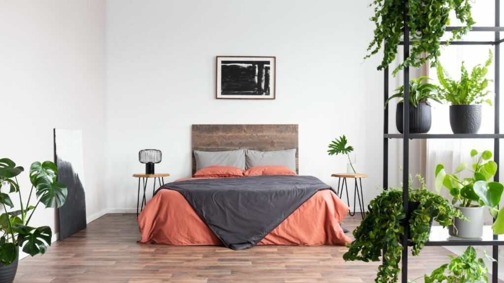 The many plants give this room an airy, spacious feel, while still being warm and inviting.  The headboard and the floor use wood to add to the rustic theme.