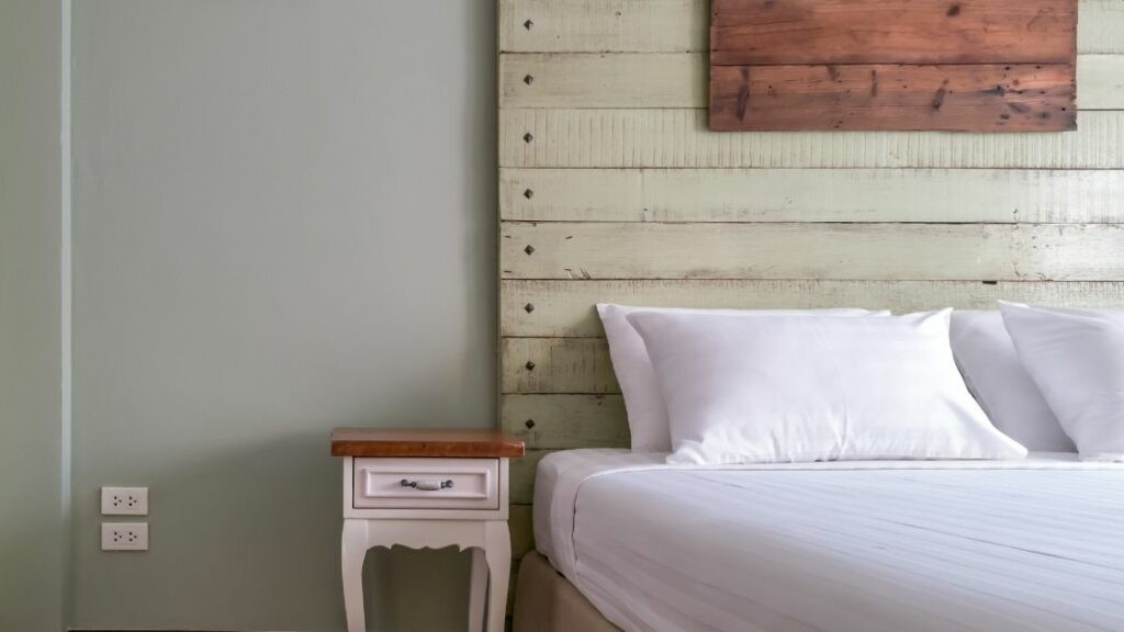 The white line and light walls are offset perfectly by the cream wood headboard.  The addition of the headboard accent matches the bedside table.